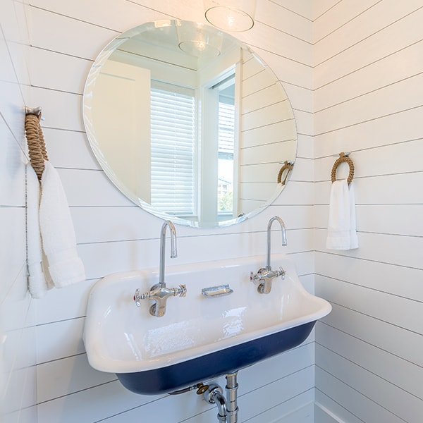 Sugar Beach Interiors, Miramar Beach, Florida. White coastal bathroom with vintage sink